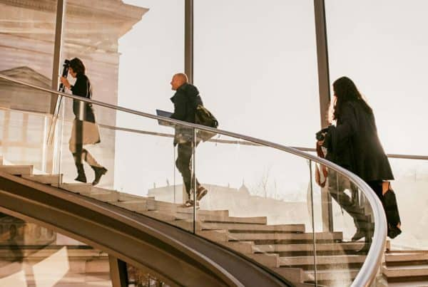 business women and men walking up a staircase
