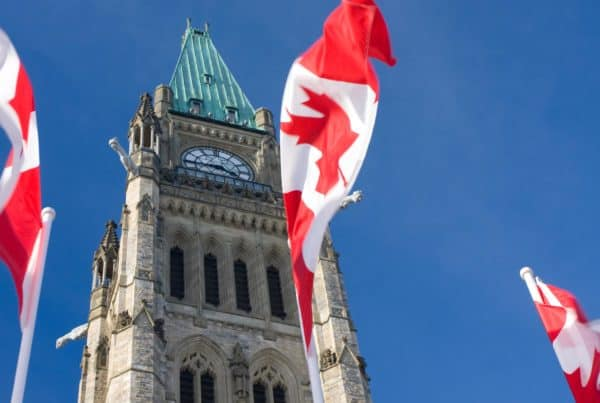 three Canadian flags in front of a clock tower